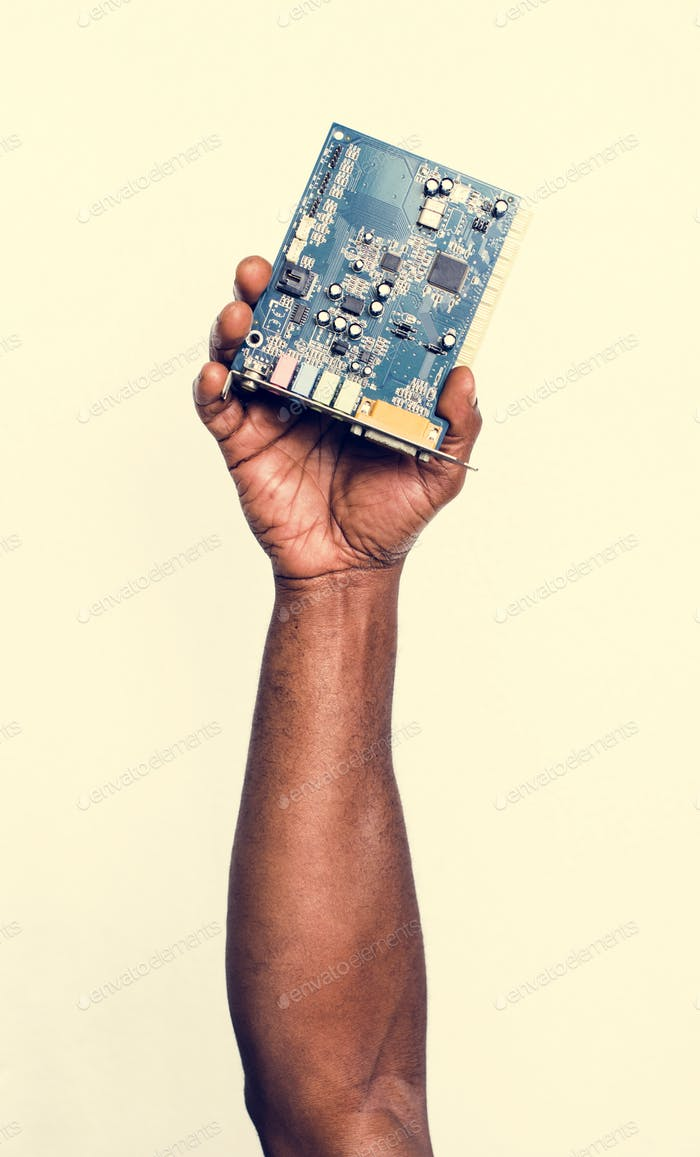Hand holding computer motherboard isolated on white