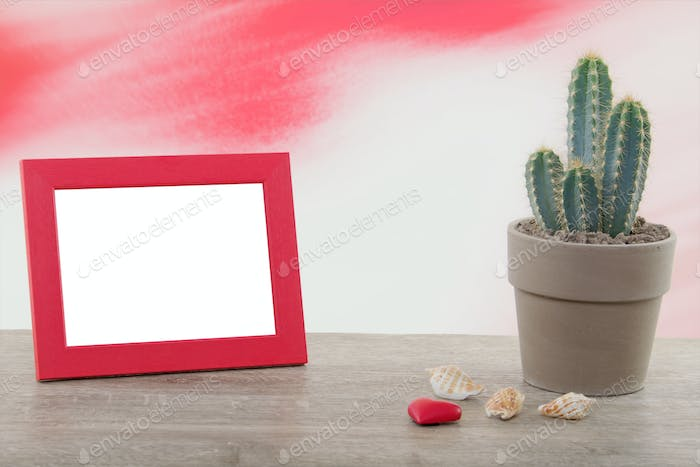 Cactus with photo frame on a wooden table