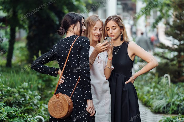 Three girls look at the photo