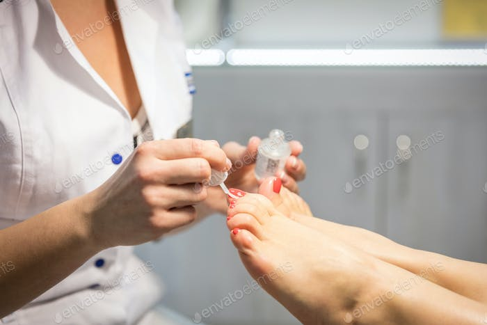 Cropped view of woman getting a pedicure at beauty salon
