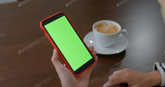 Woman use of mobile phone with green screen