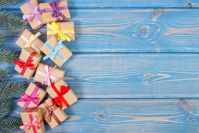 Gifts with ribbons for Christmas and spruce branches, copy space for text on old blue plank