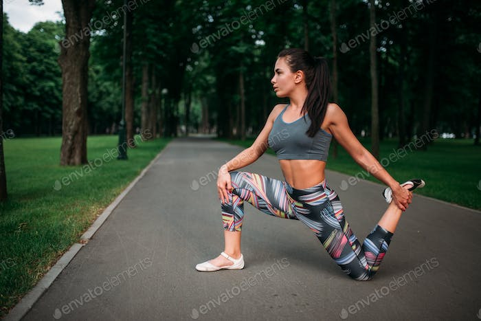 Athletic woman exercises, fitness training in park