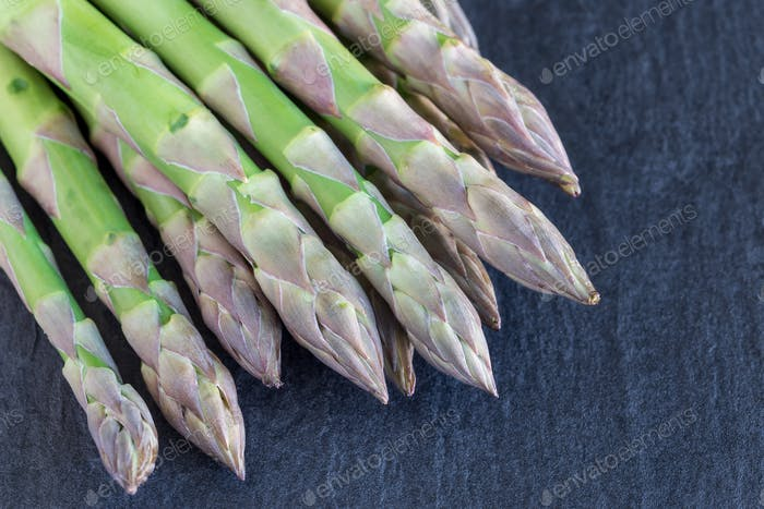 Bunch of fresh green asparagus on dark slate background, horizon