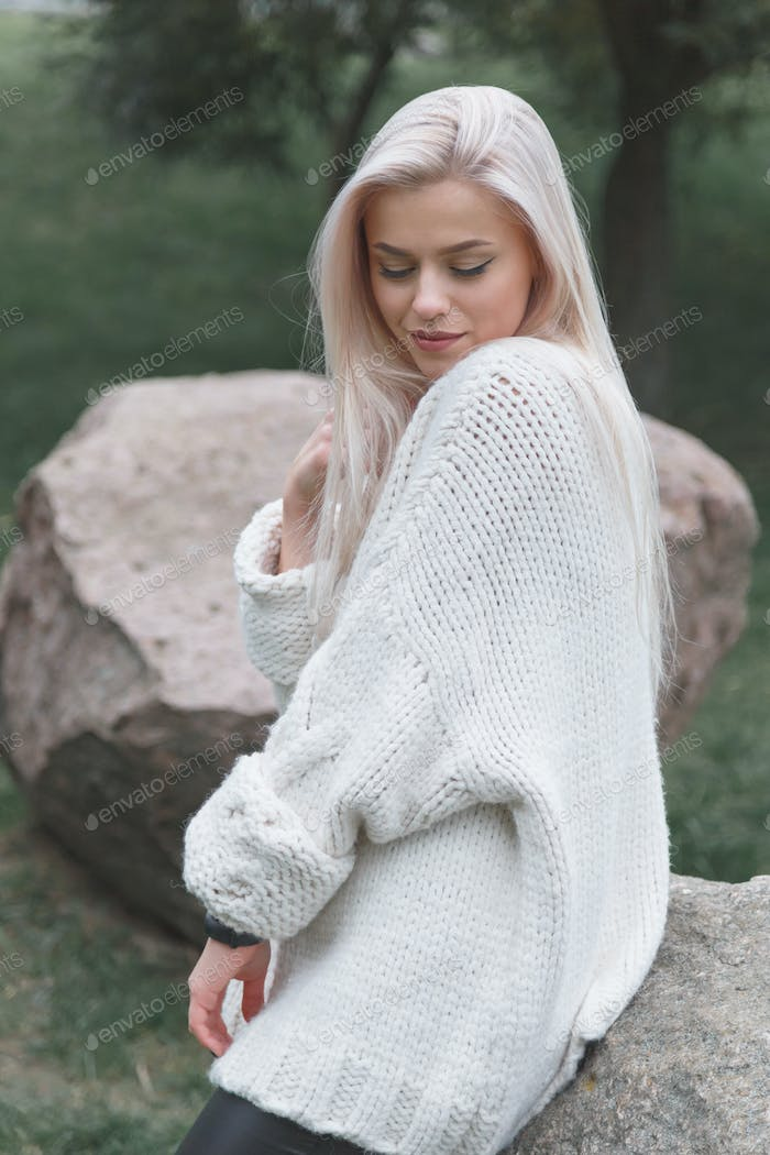 Young blonde female wearing knitted white sweater. Women fashion concept