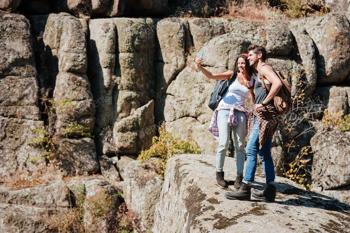 Young couple taking selfie in mountains with smartphone