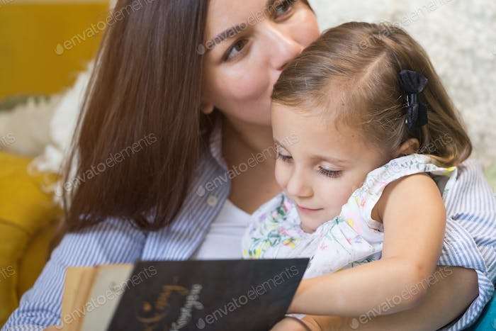 Mother with a little girl reading a book together in the house