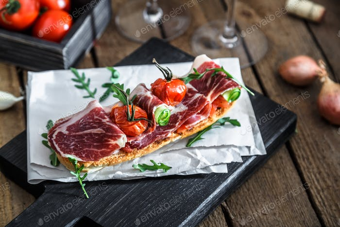 Traditional parma cured ham antipasto on wooden background, rustic style
