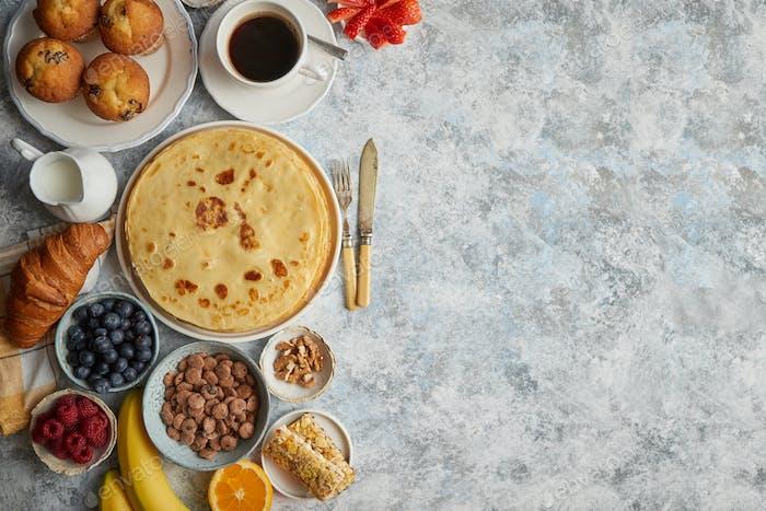 Frühstückstisch mit frischem Obst, Pfannkuchen, Kaffee, Croissants