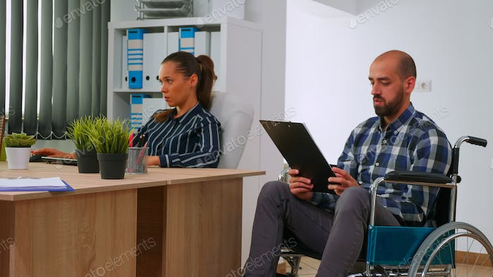 Manager in wheelchair giving advice about project to partner