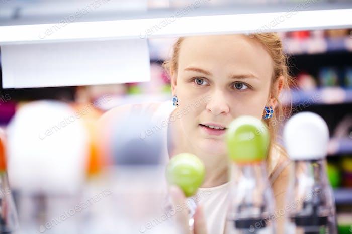Mujer joven analizando productos en una tienda