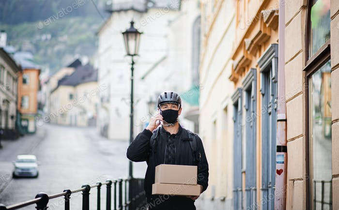 Delivery man courier with face mask and smartphone delivering parcel box in town