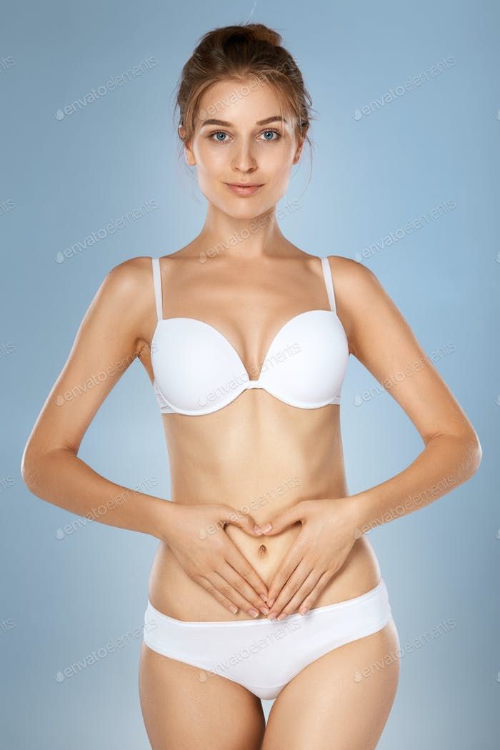 Health issues - female suffering from pain and holding her hands on the stomach