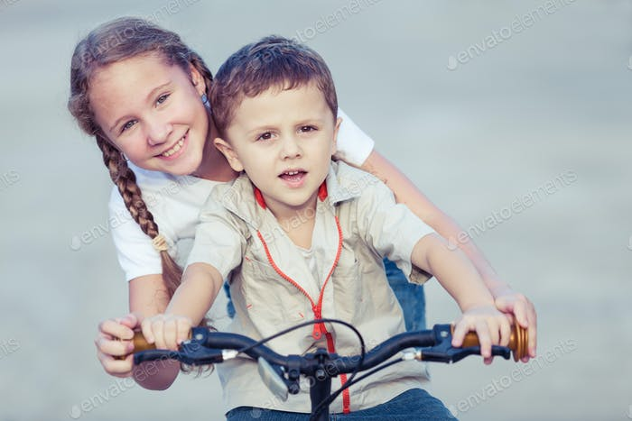 Happy kids with bike standing on the road at the day time.