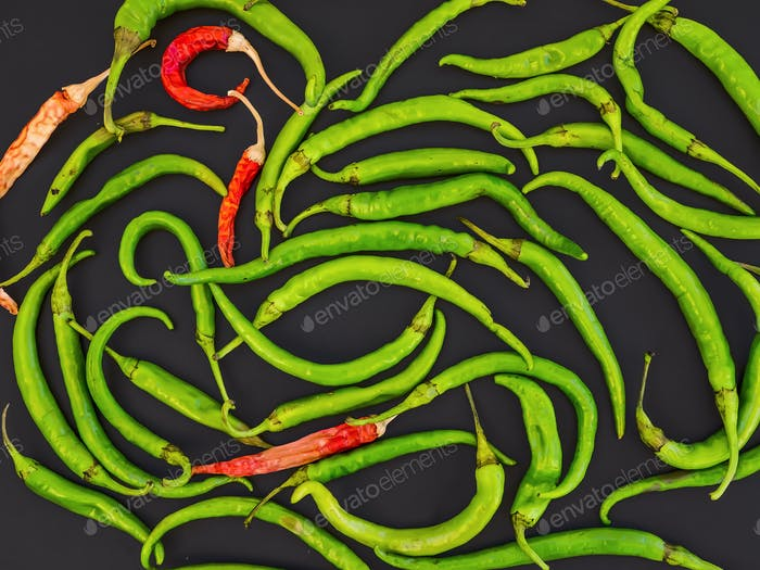 Green and red chili peppers on black