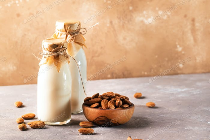 Almond milk with almond on brown table