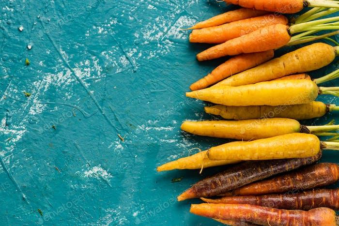 Bunte Mini-Karotten auf blauem Betonhintergrund. Leerzeichen kopieren