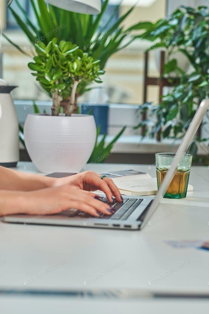 Frau mit Maniküre tippt auf Laptop