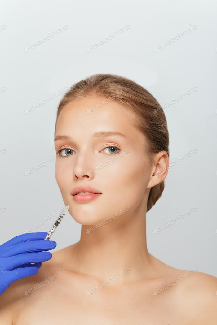 Portrait of young attractive woman getting beauty injection in m