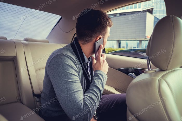 A man talking by smartphone in the car.