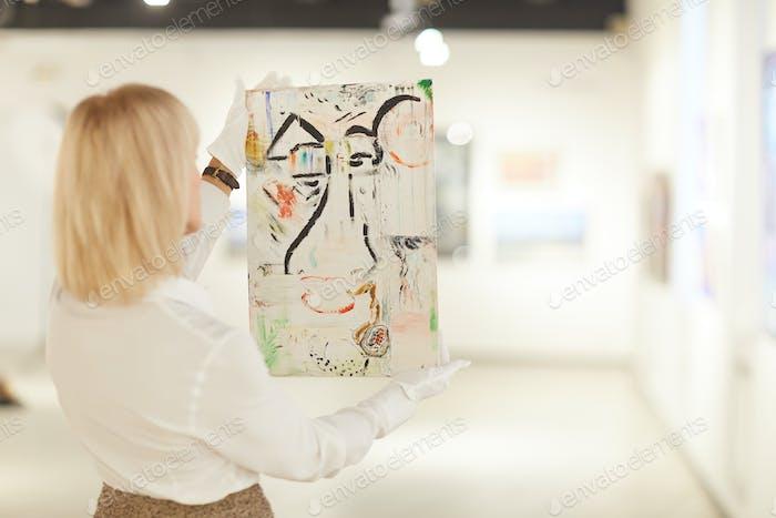 Frau hält abstrakte Malerei in Kunstgalerie