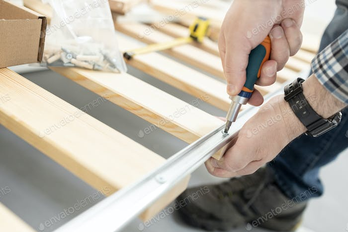 Close up of a hands Assembling a bed frame using a screwdriver