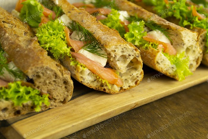 Baguette sandwiches with salmon and lettuce, close up