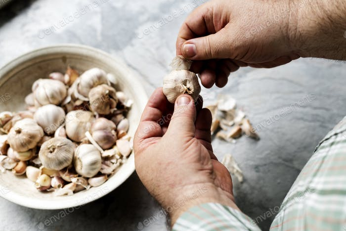 Closeup of hand peeling garlic