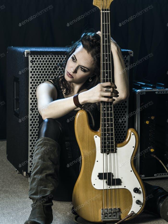 Schöne Frau Bassist sitzen mit ihr amp