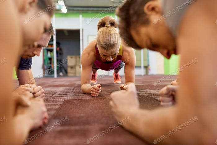 group of people doing plank exercise in gym