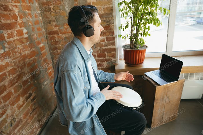 Caucasian musician playing hand drum during online concert at home isolated and quarantined