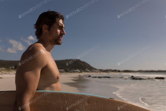Seitenansicht des Shirtless jungen männlichen Surfer mit Surfbrett steht am Strand in der Sonne