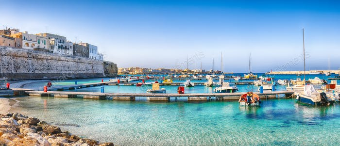 Several fishing boats at the Otranto harbour - coastal town in Puglia with turquoise sea