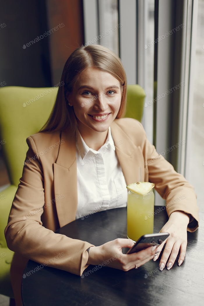 Elegant woman sitting at the table with cocktail and phone