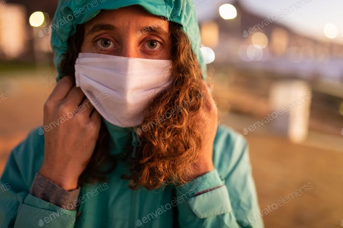 Caucasian woman wearing a protective mask against coronavirus and looking at the camera
