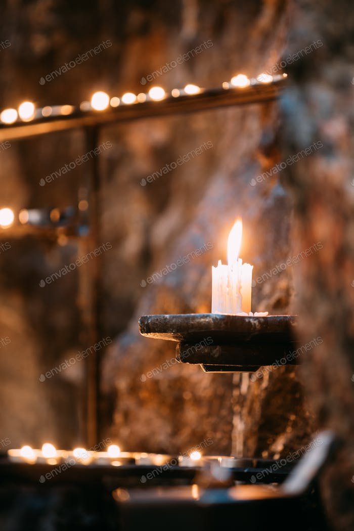 Old Candle In Church. Candle Light Flame Near Ancient Wall
