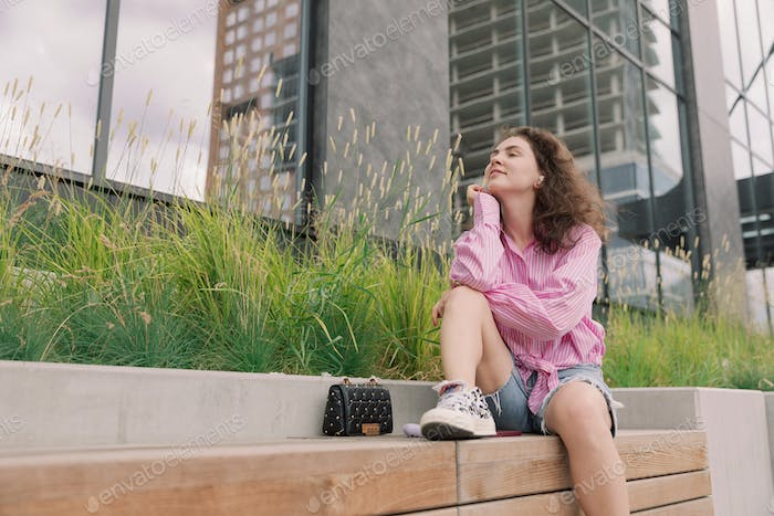Portrait of young woman listening to music with mobile phone.