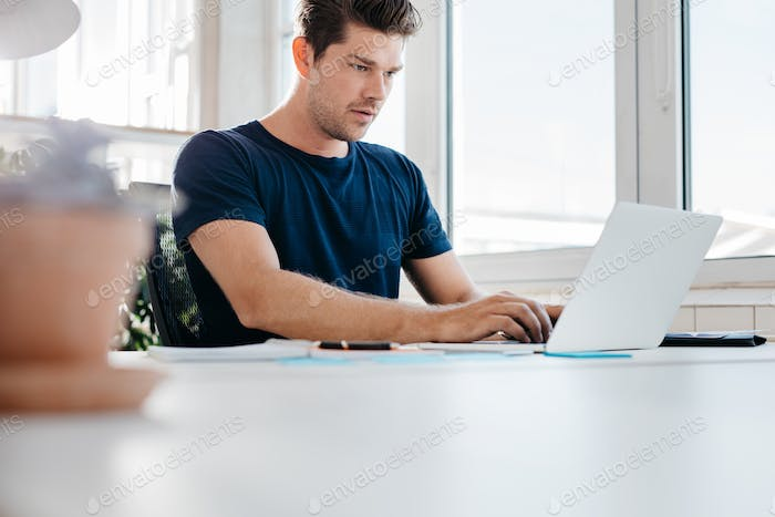 Busy young man working on laptop computer in office