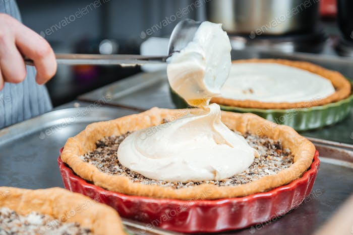 Cheif cook making traditional french pie with cream and filling