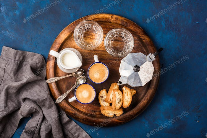 Coffee espresso, cantucci, cookies, milk and water on wooden board