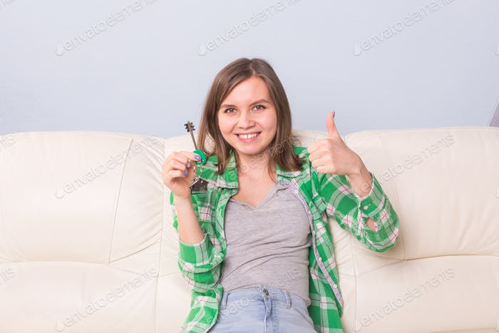 Young woman showing keys to new home