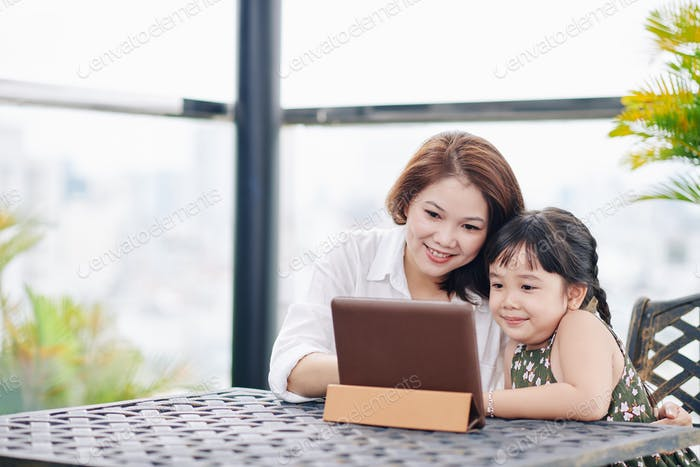 Mother and daughter watching cartoon