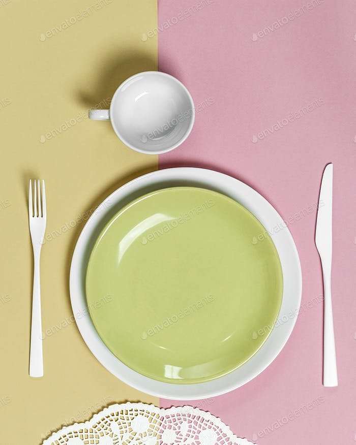 Light green plate and white cutlery on a pink-green background.