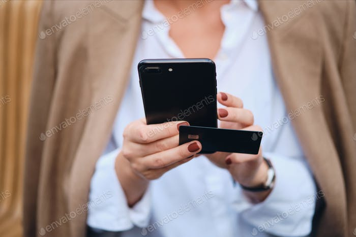 Close up businesswoman with credit card using cellphone outdoor