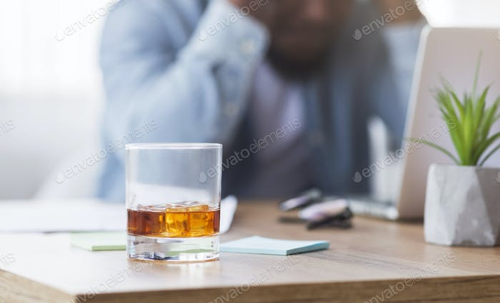Desperate black businessman suffering from bankruptcy, drinking alcohol at workplace