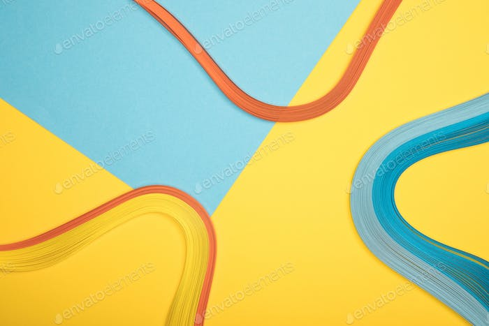 top view of curved multicolored lines on blue and yellow background