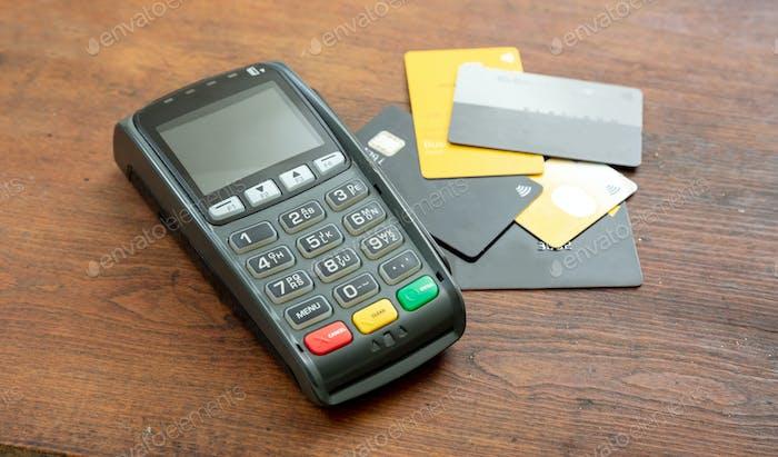 Zahlautomat, POS-Terminal und Kreditkarten auf Holzschreibtisch