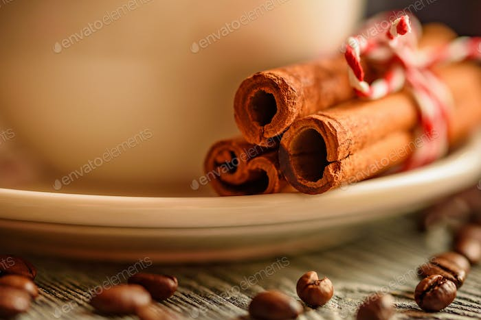 Cinnamon stick and cup of hot drink