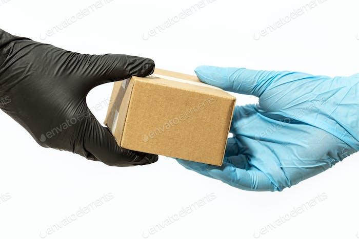 Kurier-Mann-Hand in Schutzhandschuh liefert ein Paket an einen Kunden oder Online-Käufer