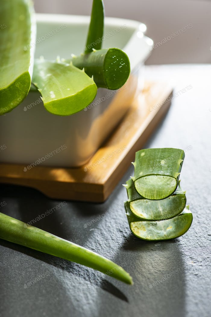 Aloe vera slices on dark background. Health and beauty concept.